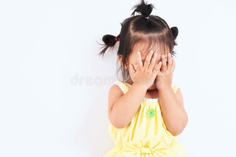 Asian baby girl closing her face and playing peekaboo or hide and seek with fun stock photography