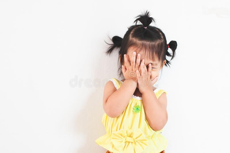 Asian baby girl closing her face and playing peekaboo or hide and seek with fun royalty free stock image