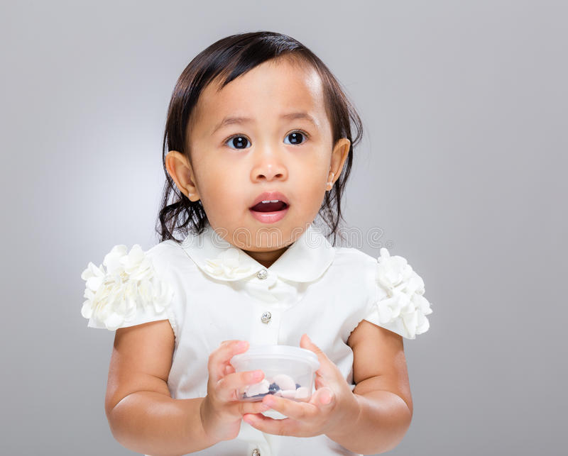 Asian baby girl confuse and hold plastic box. With gray background royalty free stock photos