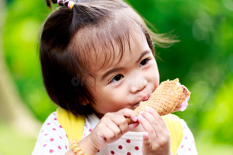 Asian baby girl eating icecream. In park stock photography