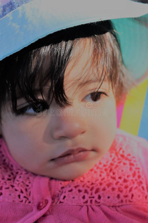 A face for a baby girl. An Asian baby girl looking far a way like she look to the future with a slight light of sun on here face royalty free stock photography
