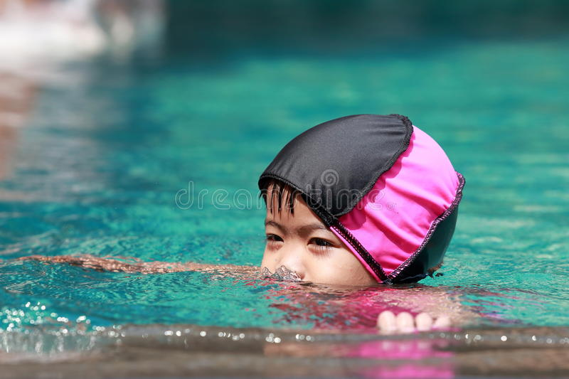 Asian baby girl playing in swimming pool stock photography