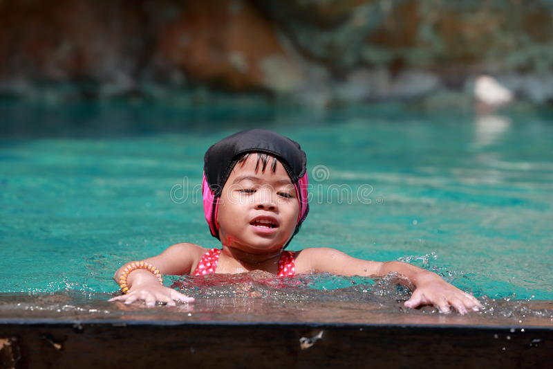 Asian baby girl playing in swimming pool royalty free stock photo