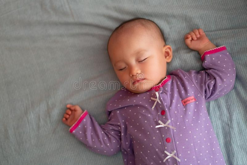 Asian baby girl sleeping blissfully on a bed stock images