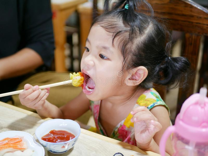 Asian baby girl tasting tomato sauce for the first time in her life stock image