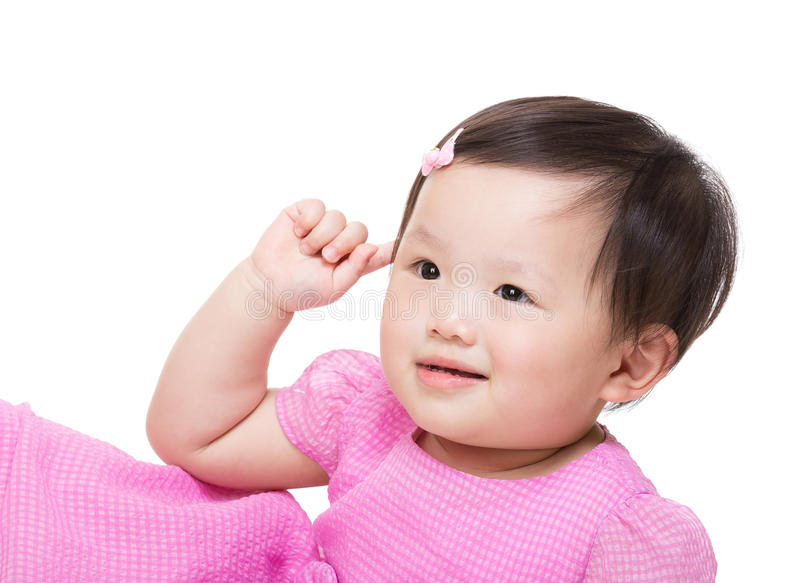 Asian baby girl touch her ear. Isolated on white stock photography