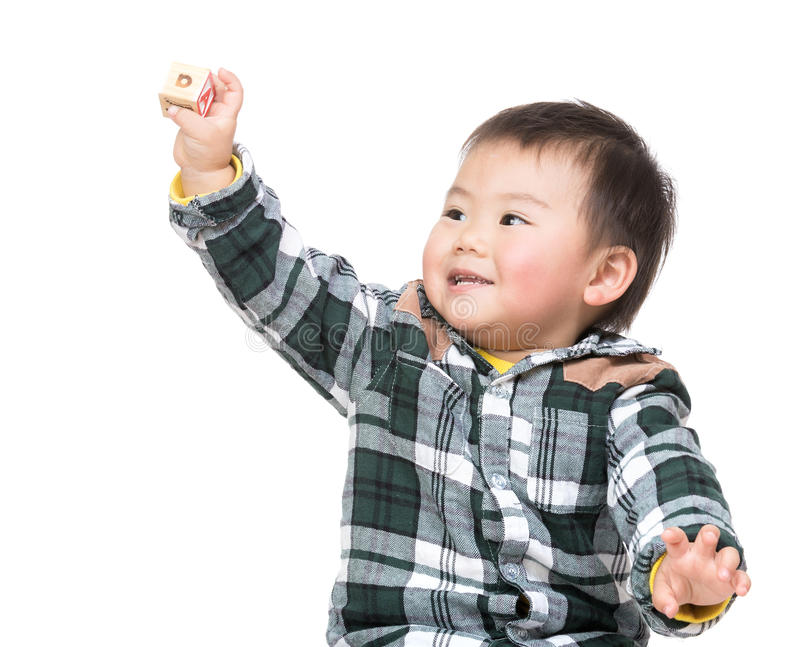 Asian baby holding toy block. Isolated on white stock image