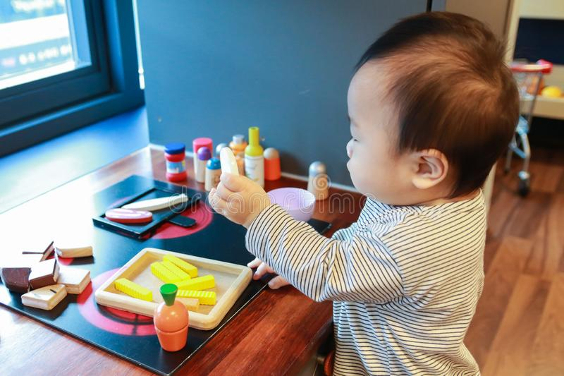 Asian baby playing alone with toy kitchen kit stock photography