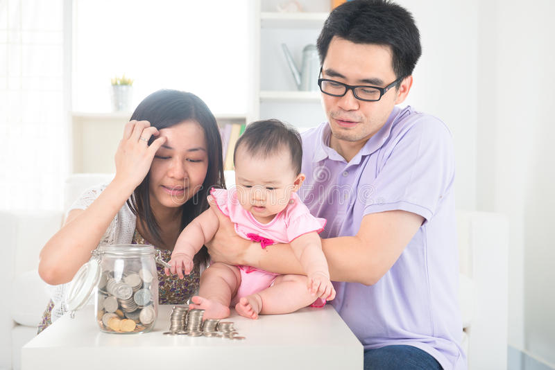 Asian baby putting coins into the glass bottle with help of pare royalty free stock photo