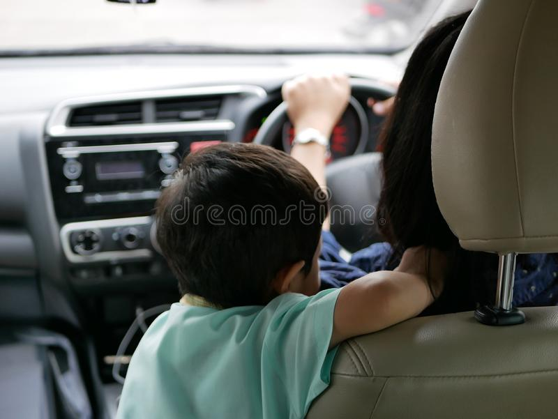 Asian baby standing on a driving car and does not fasten the seatbelt royalty free stock photos