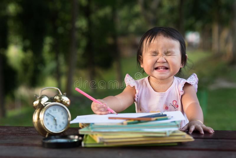 Asian baby toddler drawing at park while making funny face royalty free stock image