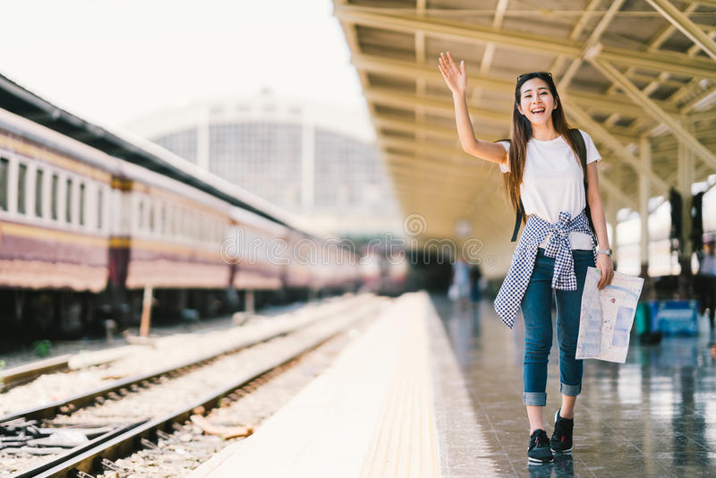 Asian backpack traveler woman holding generic local map and waving hand at train station platform summer holiday traveling concept stock images