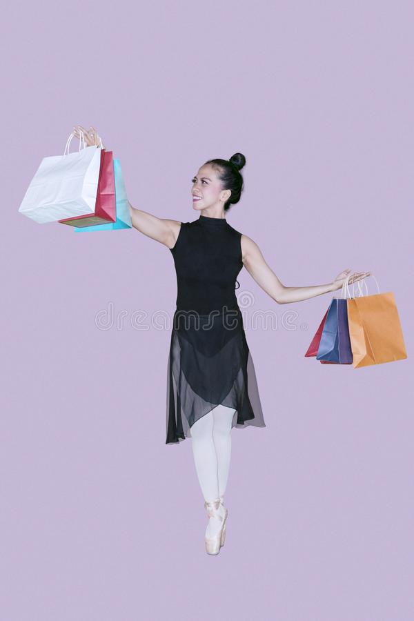 Asian ballerina carrying paper bags royalty free stock photography