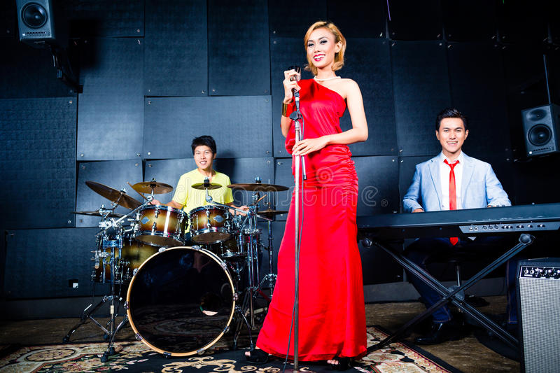 Asian band recording song in studio. Asian professional singer drummer and keyboarder recording new song or album in studio royalty free stock image