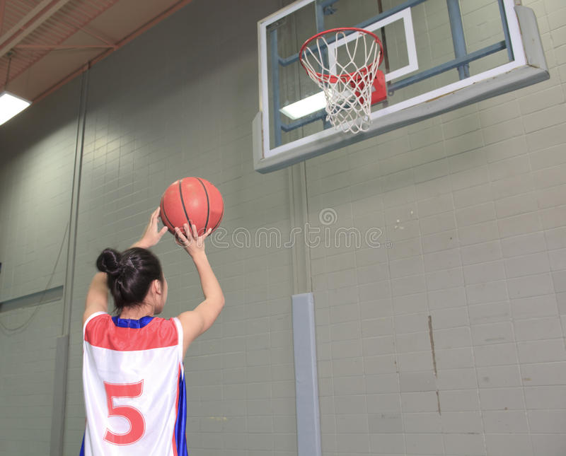 A asian basketball player in gymnase field. Try to make a goal stock photography