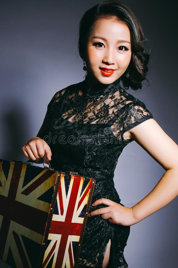 Asian beauties wear cheongsam and carry suitcases. A happy smile. royalty free stock images