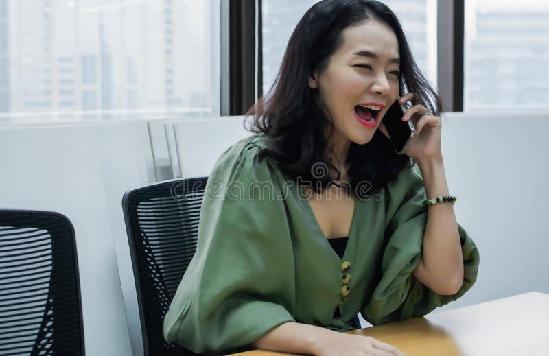 An asian beautiful woman is complaining someone on mobile phone royalty free stock image