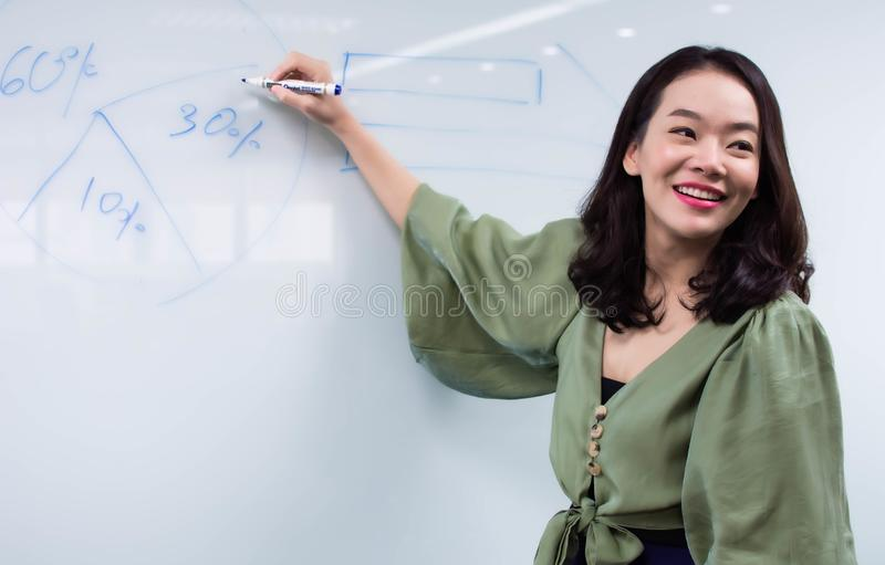 An asian beautiful business woman is presenting her sale planing royalty free stock photography