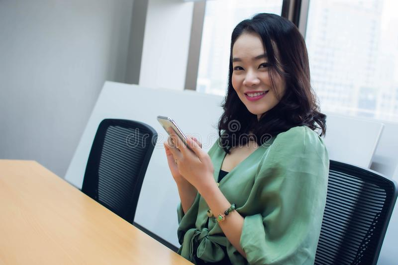 An asian beautiful business woman is posing with her mobile phone royalty free stock images