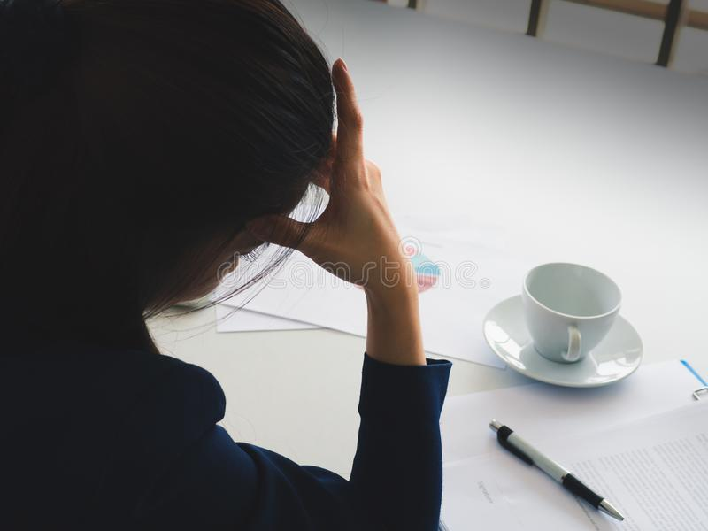Asian long hair beautiful business woman in navy blue suit strain with work util headache in her office. Have coffee cup, pen, rep royalty free stock photography