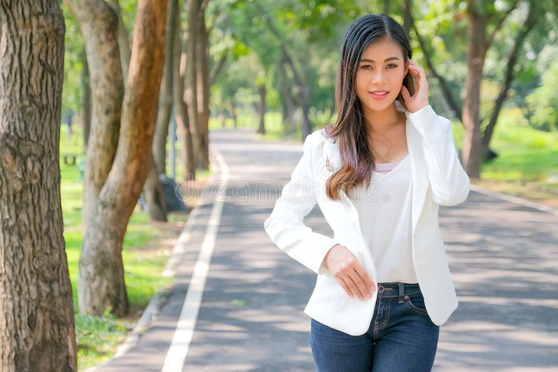 Asian beautiful business woman with white suit stand on the road in the garden with the concept the success way for professional royalty free stock photography