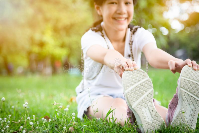 Asian beautiful child girl stretching legs while sitting in park, female teenager warming up before running,exercise in morning, royalty free stock images