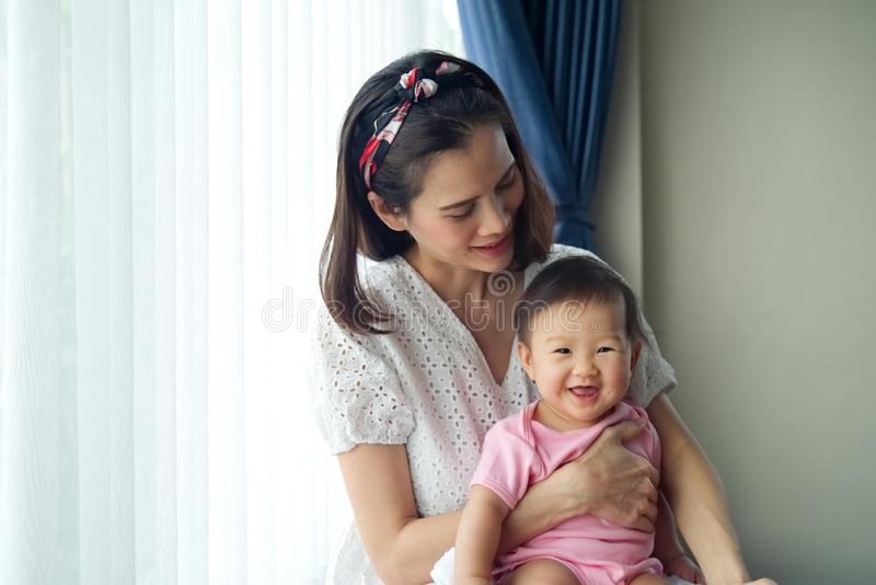 Asian beautiful mother holding her cute baby in her arms sitting near the window at home. royalty free stock photography