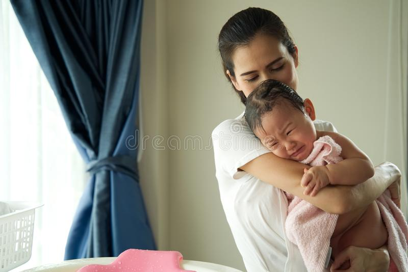 Asian beautiful mother holding little cute crying baby after taking a bath standing in the room. royalty free stock photo