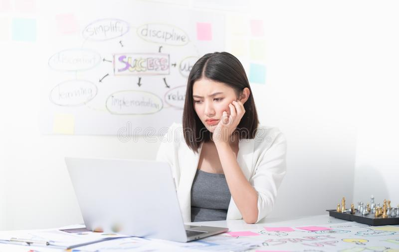 Asian beautiful office worker looks stressed and frustrated while working typing and solving problem on the laptop in the white royalty free stock photography