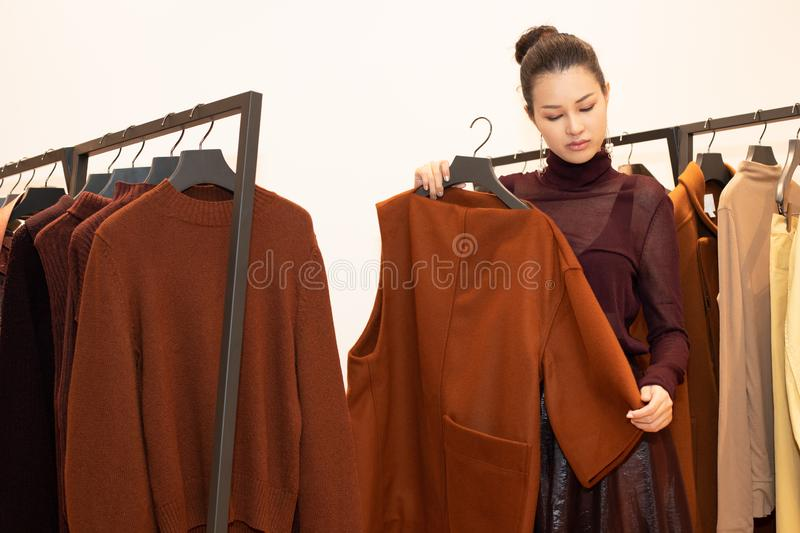 Woman in dress select new collection on rack royalty free stock image