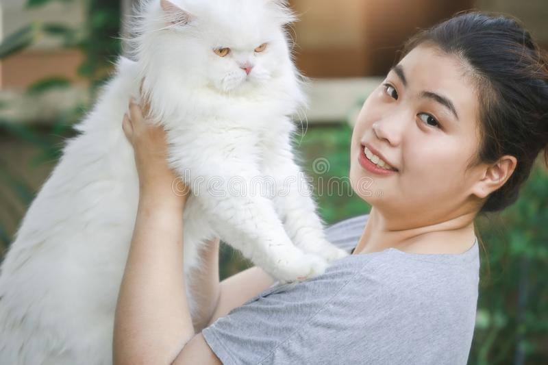 Asian beautiful woman cuddling carry white persian cat Long hair on nature blurred background for lifestyle in home with stock photos