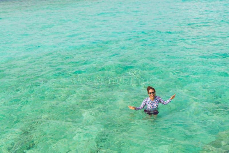 Asian beautiful woman is enjoyful in the lagoon sea background royalty free stock image