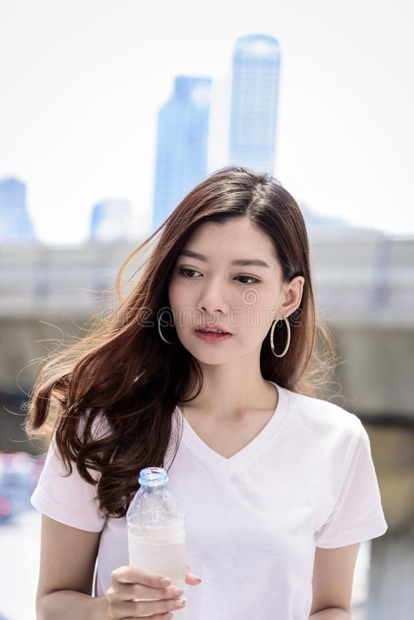 Asian beautiful woman has water drinking with city background in stock images