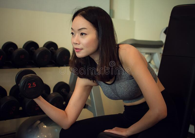 A Asian beautiful woman is holding dumbbell royalty free stock image