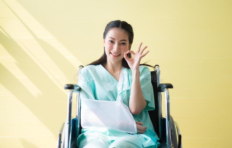 Asian beautiful woman patients raise up your hand OK sign symbol and sitting on wheelchair at hospital,Happy and smiling royalty free stock photography