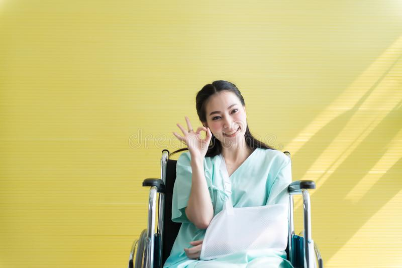 Asian beautiful woman patients raise up your hand OK sign symbol and sitting on wheelchair at hospital,Happy and smiling royalty free stock image