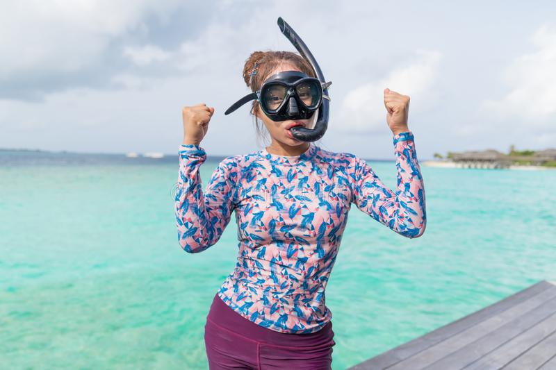 Asian beautiful woman is snorkeling in the lagoon sea background stock image