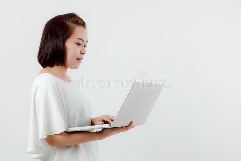 Asian beautiful woman Standing in a white shirt in her hand Holding a laptop computer Stand smiling happily With a white stock image