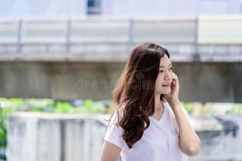 Asian beautiful woman tourist has music listening with headphone stock photography