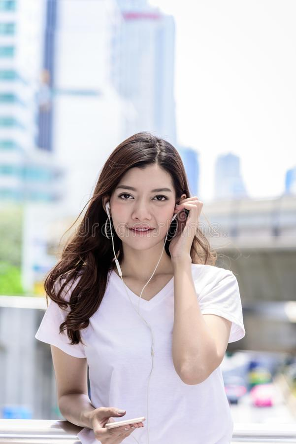 Asian beautiful woman tourist has music listening with headphone royalty free stock images