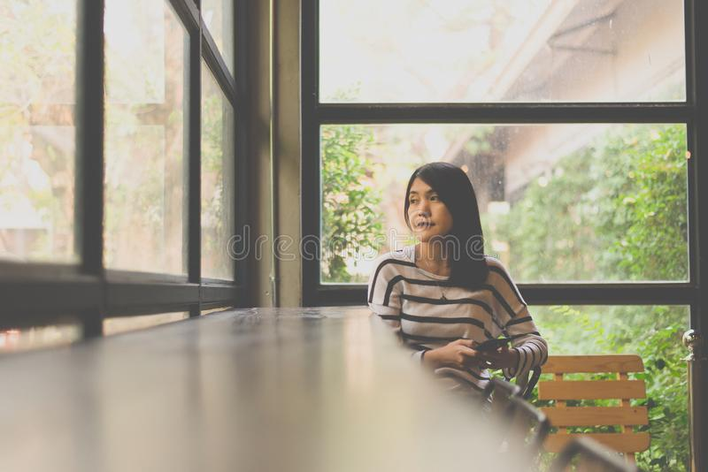 Asian beautiful woman using smart phone in modern coffee shop cafe,Happy and smiling,Positive thinking vintage color tone royalty free stock image