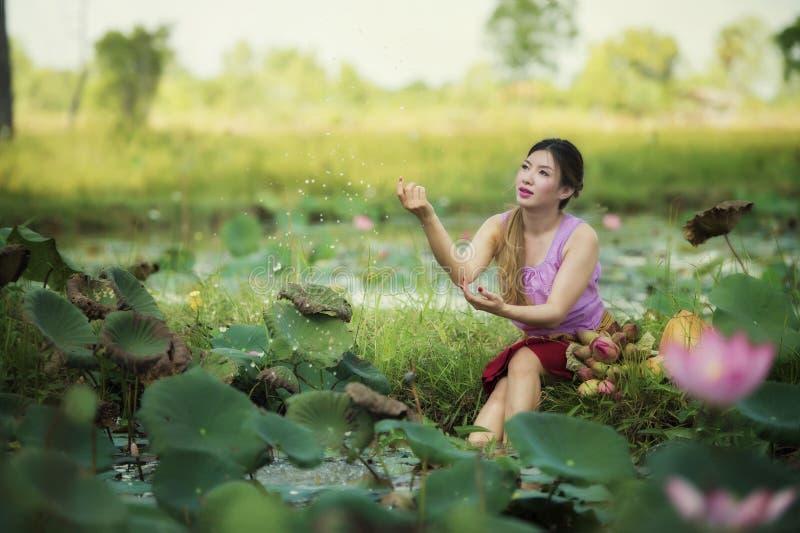 Asian beautiful woman walking in lotus field. royalty free stock photo