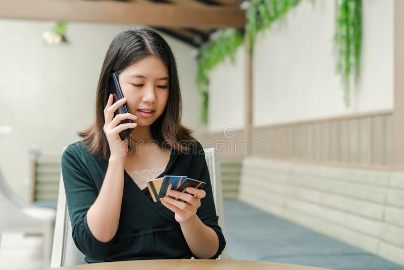 Asian beautiful woman Wearing a black shirt Sitting in the house There is a credit card in your hand and you are holding the phone royalty free stock photos