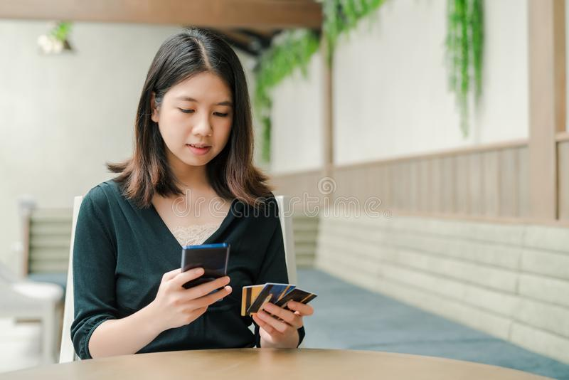 Asian beautiful woman Wearing a black shirt Sitting in the house There is a credit card in your hand and you are holding the phone stock images