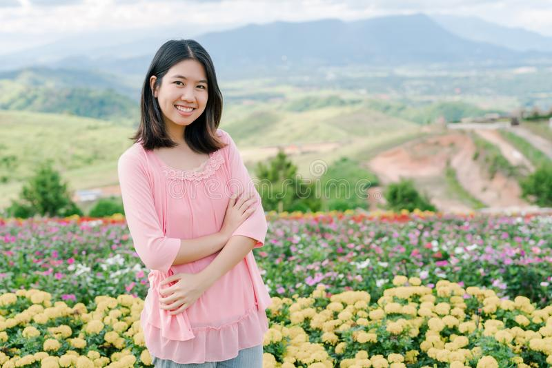 Asian beautiful woman Wearing a pink shirt Standing happily smiling in a yellow flower garden Behind is a mountain view royalty free stock images