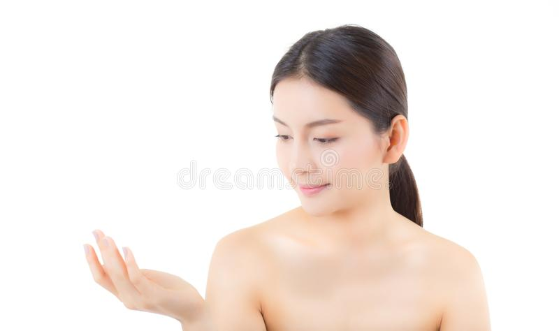 Asian beautiful young woman showing with healthy clean skin presenting something empty copy space on the hand isolated. On white background, beauty concept royalty free stock image