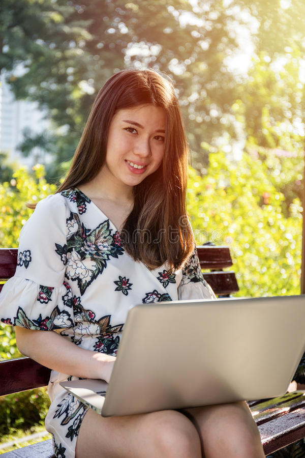 Asian beautiful young woman sitting on the bench with laptop stock photography