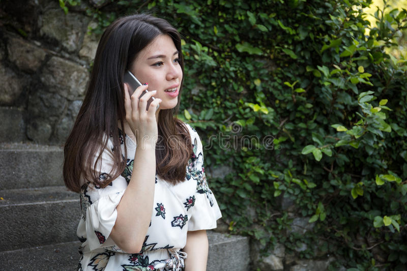 Asian beautiful young woman talking on the phone royalty free stock photography