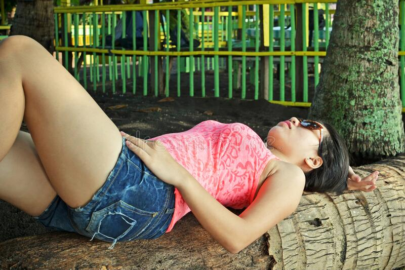 Laying on a tree. Asian beauty laying on a tree on a tropical beach royalty free stock images