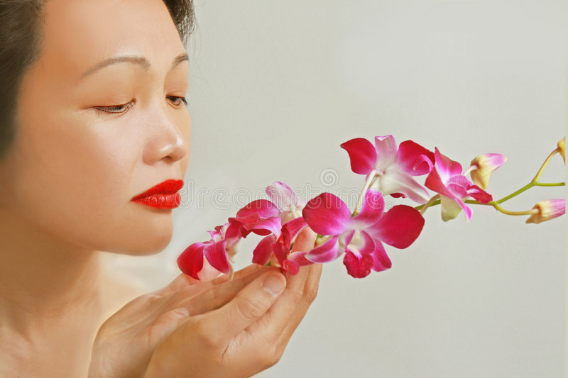 Asian beauty with orchids stock photography
